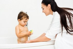 Mother washing son with yellow bath