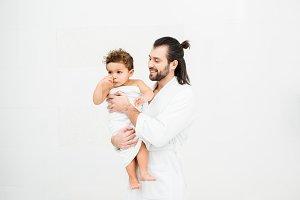Dad in bathrobe smiling to toddler s