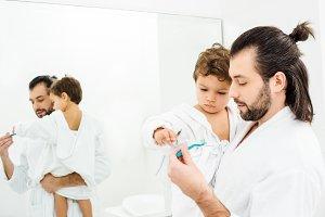 Toddler son looking at toothbrush wi