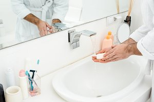 cropped view of man washing hands wi