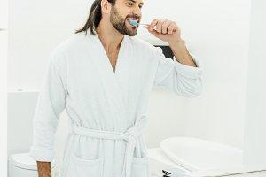 handsome adult man brushing teeth in