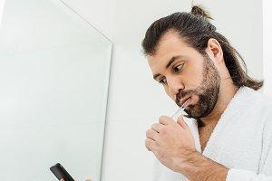 handsome adult man brushing teeth an