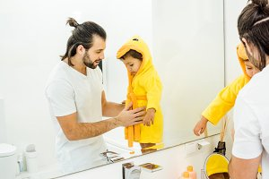 cheerful dad touching toddler son in