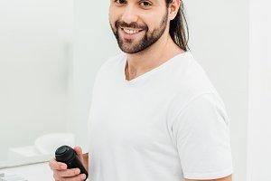 Man holding shaving foam and smiling