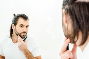 Man looking in mirror and shaving is