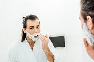 Young man applying shaving foam in f