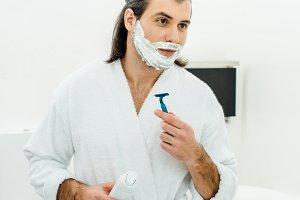 Man in white bathrobe shaving in fro