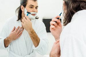 Man smiling and shaving in front of