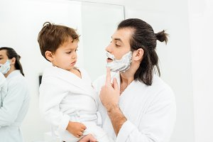 Father showing toddler son shaving f