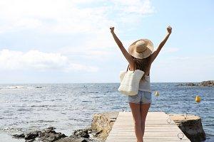 Single tourist raising arms on beach
