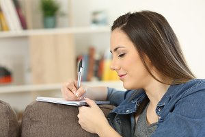 Serious woman writing notes at home