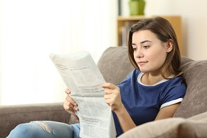 Serious teenager reading a newspaper