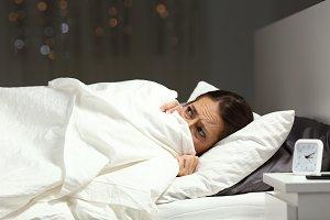 Scared woman hiding under blanket
