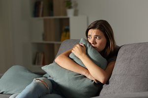 Scared teen at home embracing pillow