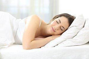 Satisfied woman sleeping in a bed
