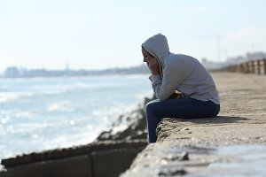 Sad teenager girl alone on the beach