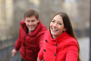 Happy couple in red running outdoors
