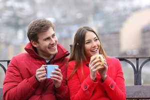 Happy couple drinking hot drinks