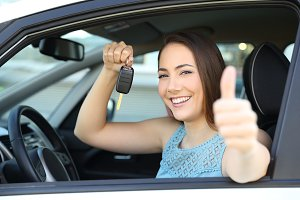 Happy car owner with a key and thumb