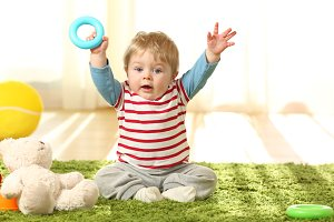 Happy baby raising arms with a toy