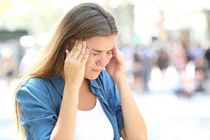 Girl suffering migraine in the stree