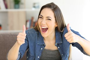 Excited woman with thumbs up at home