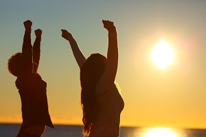 Excited friends raising arms at suns