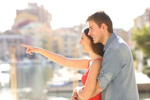 Couple pointing away in the street