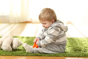 Baby playing alone with toys