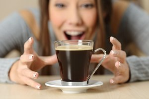 Amazed woman looking at a coffee cup