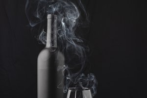 Black wine bottle and cigar smoke