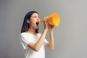 Young woman holding paper megaphone