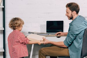 happy man giving book to little son