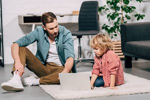 father and son sitting on floor with