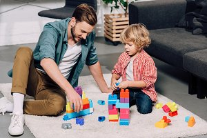 man with little son playing with col