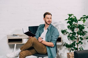 pensive male freelancer sitting with