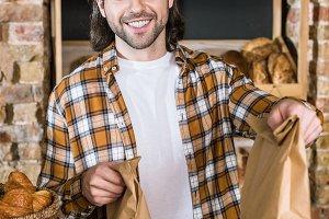 Smiling male seller holding paper ba