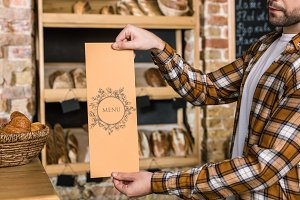 male seller holding paper menu in ha