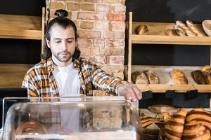 handsome adult seller working at bak