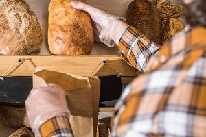 Male seller taking freshly baked bre
