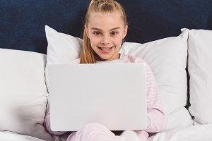 Cheerful preteen child using laptop