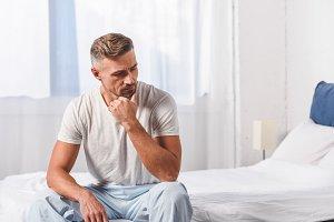 Thoughtful man sitting in pyjamas on