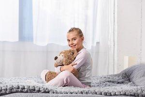 Cheerful kid holding teddy bear and