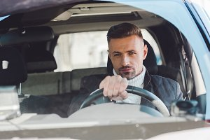 Handsome man sitting in car and hold