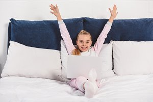Cheerful preteen child lying in bed