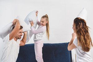 Cheerful parents having pillow fight