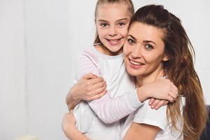 Mother and daughter hugging and smil