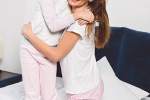 Mom and daughter hugging and smiling