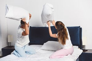 Cheerful couple having pillow fight