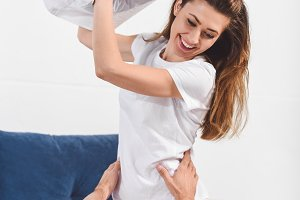 Cheerful wife having pillow fight wi